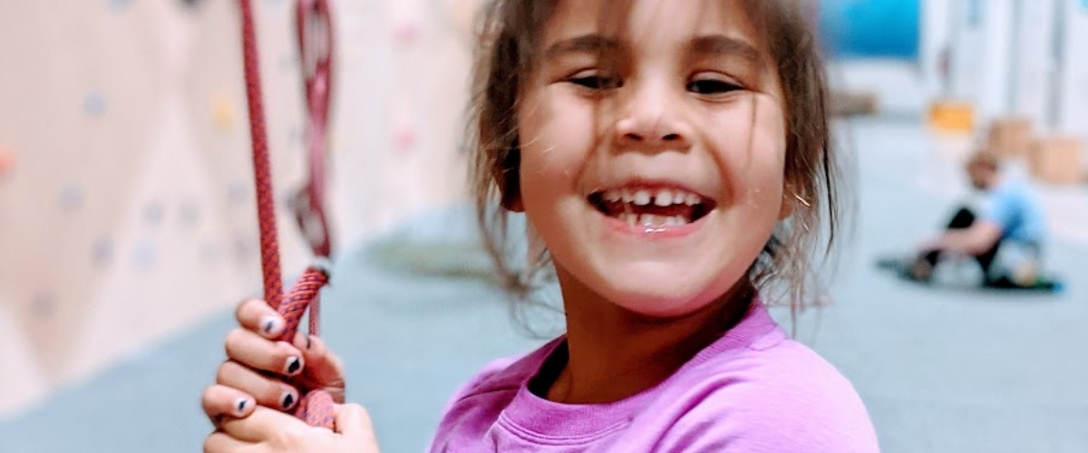 Young girl smiling at climbing gym