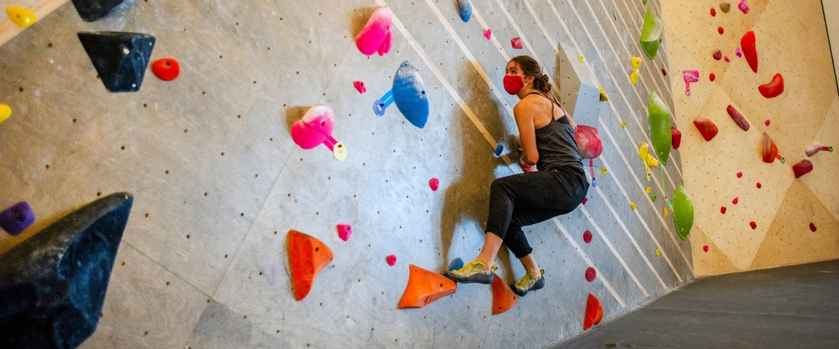 Woman climbing indoors in mask