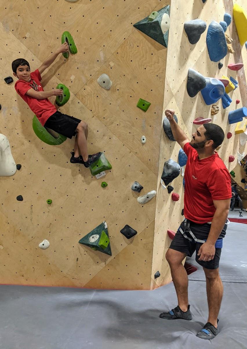 Child rock climbing next to parent