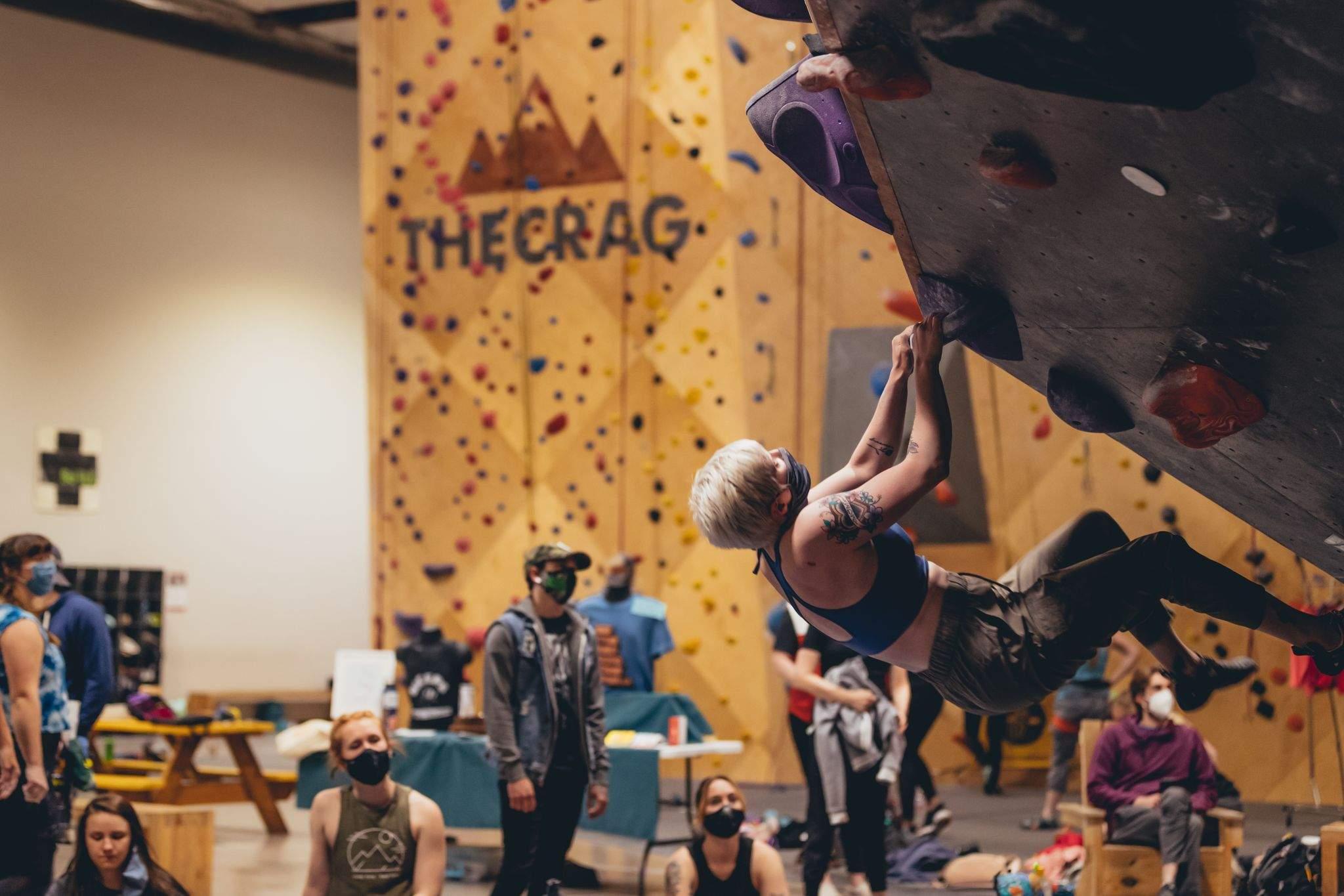 Woman rock climbing inside wearing mask