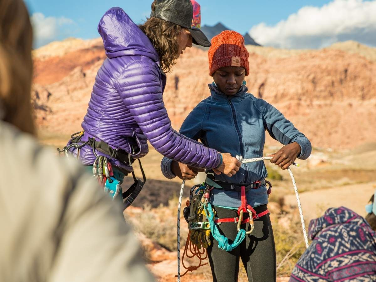 Young rock climber being taught outdoors