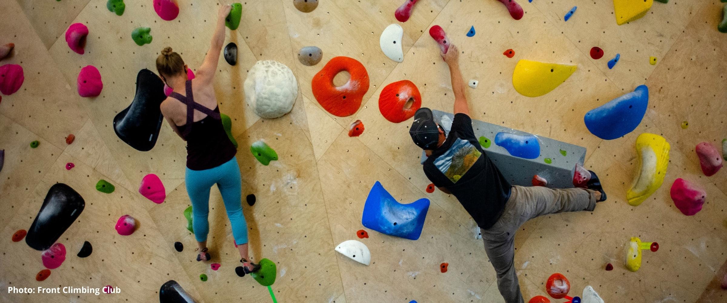 Climbers traversing a bouldering wall