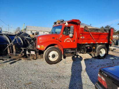 Red dump truck in gravel lot.
